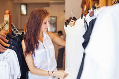 Woman putting a dress to a shelve in shop Royalty Free Stock Photography