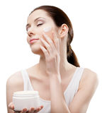 Woman applying emollient cream from container on face Stock Images