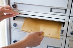 Woman putting envelope in mailbox Stock Photo