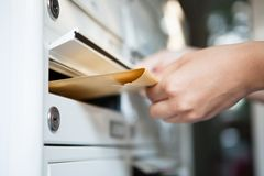 Woman putting envelope in mailbox Royalty Free Stock Image