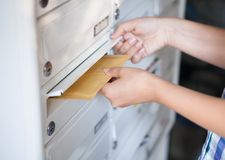 Woman putting envelope in mailbox. Close-up of woman's hand holding envelope and inserting in mailbox Stock Images