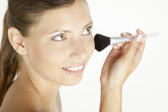 Woman putting on face powder. Portrait of young woman putting on face powder Royalty Free Stock Image