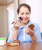 Woman putting facepowder on  face Royalty Free Stock Photo