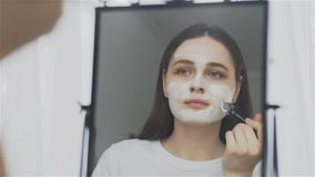 Woman putting facial mask on her face in front of the mirror. HD stock video footage
