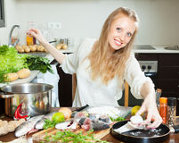 Woman putting  fish in flour into  pan Stock Photography