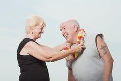 Woman putting a flower garland on husband Stock Photos