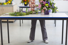 Woman putting flowers into floral arrangement in classroom Royalty Free Stock Photography