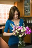 Woman putting flowers in vase Royalty Free Stock Images
