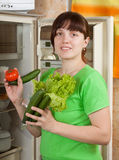 Woman putting fresh vegetables   into refrigerator Royalty Free Stock Photo