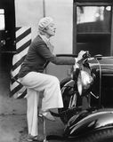 Woman putting gas in the front of her car Stock Photography