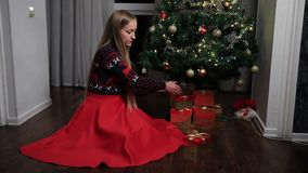 Woman putting gift boxes under Christmas tree stock footage