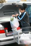 Woman putting groceries in trunk Royalty Free Stock Photos