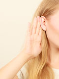 Woman putting hand ear to hear better Stock Images