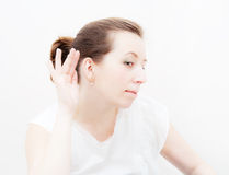 Woman putting hand to her ear Stock Images