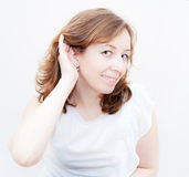 Woman putting hand to her ear Royalty Free Stock Photo