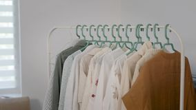 Woman is putting hanger with clothes on bar in room of modern flat in daytime, detail view of hand. Fashion female wardrobe stock video footage