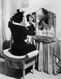 Woman putting on a hat in front of a dressing table. (All persons depicted are no longer living and no estate exists. Supplier grants that there will be no royalty free stock photos