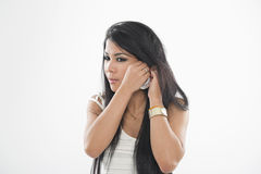 Woman putting on her earring Royalty Free Stock Photography