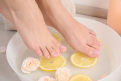 Woman putting her feet into bowl with water, roses and lemon slices on floor, closeup. stock photo