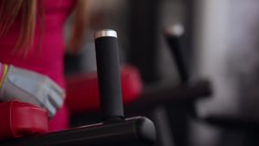 Woman putting her hands on sport equipment in the gym as she is getting ready for working out. Close-up stock video