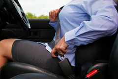 Woman putting on her seat belt Stock Photography