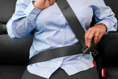 Woman putting on her seat belt Stock Image
