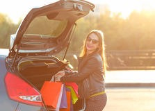 Woman putting her shopping bags into the car trunk Royalty Free Stock Photos