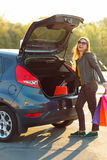Woman putting her shopping bags into the car trunk Stock Photos