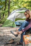 Woman putting on hiking boots at campsite with tent in backgroun. Adult female putting on hiking boots outside in front of tent Royalty Free Stock Photo