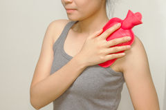Woman putting a hot pack on her shoulder pain Royalty Free Stock Photos