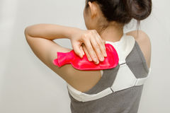 Woman putting a hot pack on her shoulder pain Stock Photography