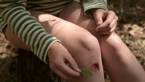 Woman putting a leaf on a wound stock video footage