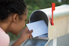 Woman Putting Letter In Mailbox. Close-up Of Woman Putting Letter In Mailbox royalty free stock image