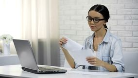 Woman putting letter to envelope sitting at home, filling out tax statement. Stock photo royalty free stock photos