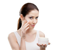 Woman putting on lifting cream from container on face Royalty Free Stock Photo