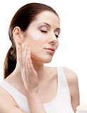 Woman putting on lifting cream on her face Stock Images