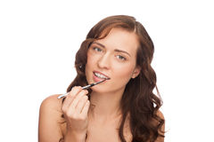 Woman putting on lip gloss Royalty Free Stock Photos