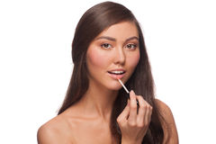 Woman putting on lip gloss Stock Images