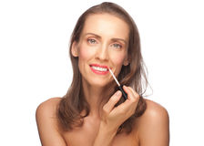 Woman putting on lip gloss Stock Photos