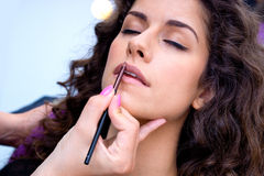Woman putting lip gloss Royalty Free Stock Images