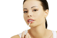 Woman putting on lip gloss Stock Photography