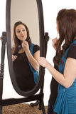 Woman putting on lip gloss mirror royalty free stock photography