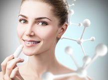 Woman putting lipbalm in big molecules chain. Beautiful young woman putting lipbalm in big molecules chain over gray background. Innovation cosmetics concept Stock Photography