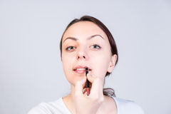 Woman Putting Lipstick Against White Background Royalty Free Stock Image