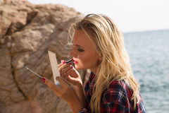 Woman putting on lipstick on the beach Royalty Free Stock Photos
