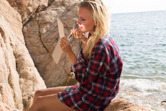 Woman putting on lipstick on the beach Stock Image