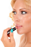 Woman putting lipstick on. Royalty Free Stock Images