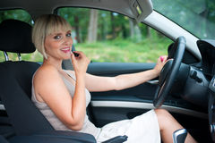 Woman putting lipstick in car Stock Photo