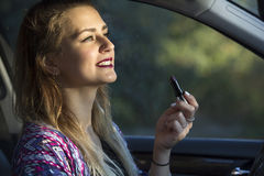 Woman putting on lipstick in car Stock Photo