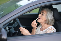 Woman putting lipstick in the car Stock Photography
